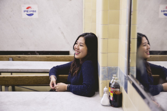 Photo of Brenda at a classic fish & chips shop - she's smiling and looking off into the distance.