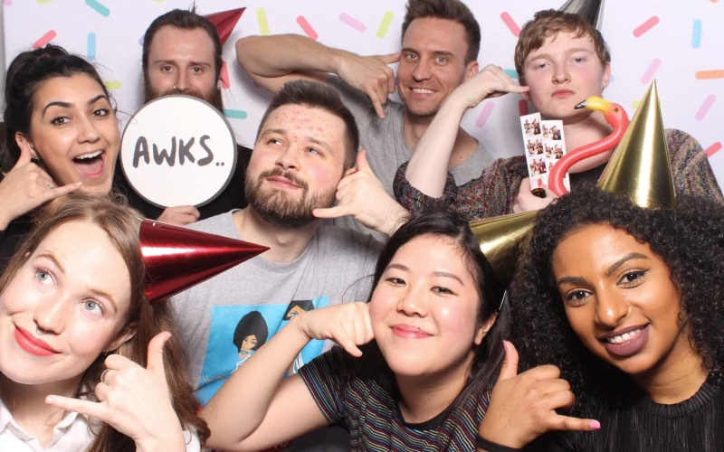 A group of people all making the 'call me' sign with their hands, some of them wearing party hats. Team Call and the Gang having shenanigans at Monzo's 4th Birthday party!