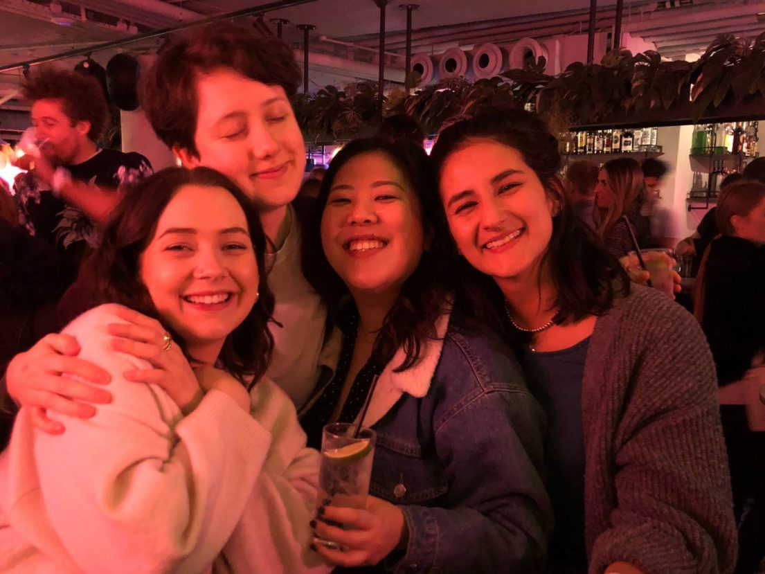 Four women at a bar. It's dimly lit with dusky red. Three of them are looking at the camera and smiling, and one of them has their eyes closed and smiling. The one in the middle is carrying a gin and tonic with glee.
