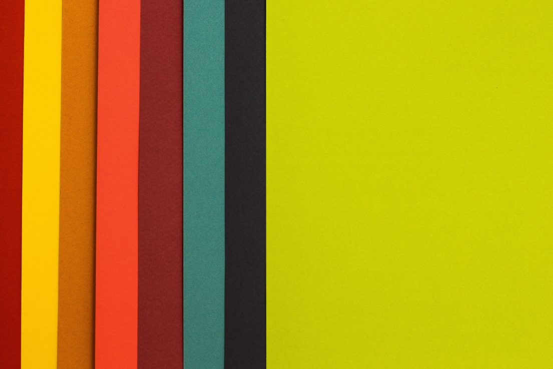folders in rainbow colours, neatly arranged overlapping each other from left to right.